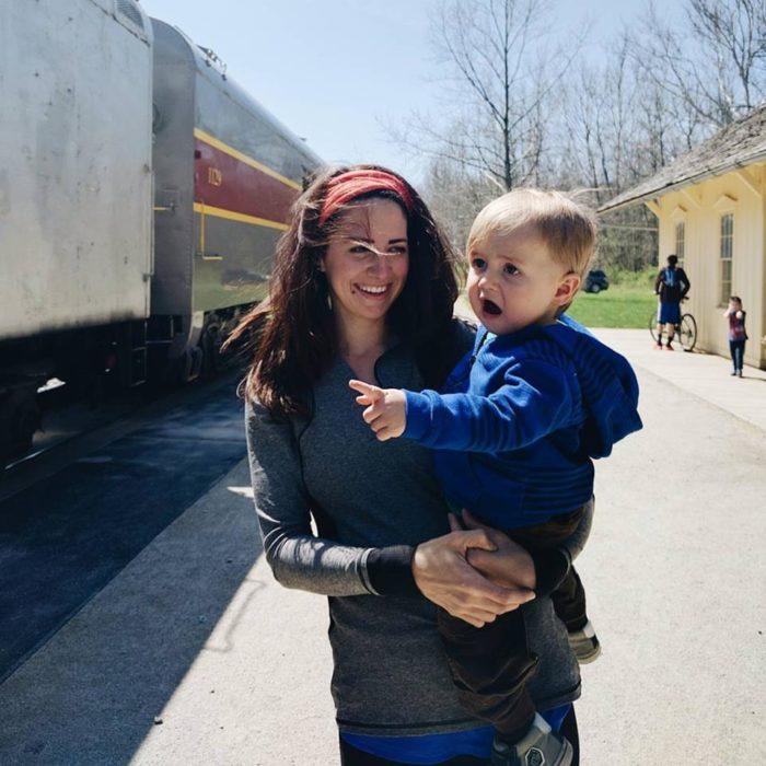 fotografía de una mujer cargando a su bebé sorprendido por ver un tren por primera vez