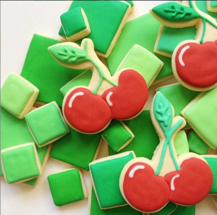 galletas en forma de cuadros verdes con algunas galletas en forma de cerezas