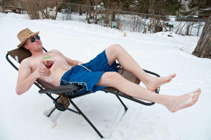 hombre en la nieve tomando un cocktail