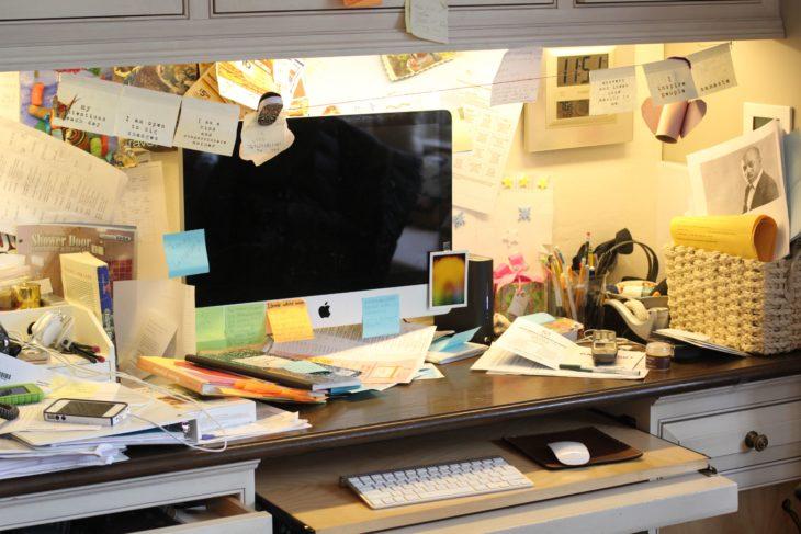 Escritorio desorganizado con postit en todas partes y hojas tiradas