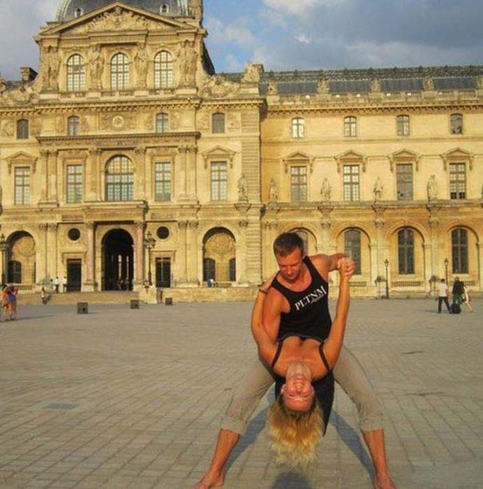 fotografía de una pareja bailando frente a un edificio histórico