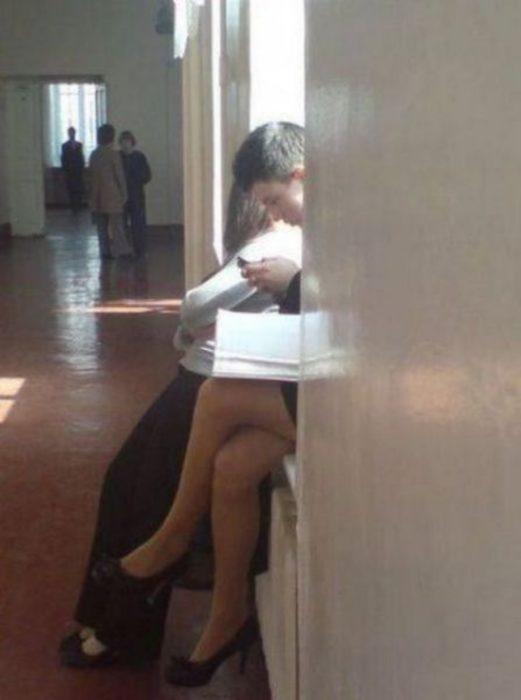 piernas de una chica con la cabeza de un chico escribiendo