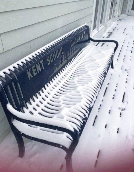 nieve sobre una banca en una calle