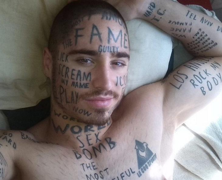 hombre todo tatuado con frases en su rostro