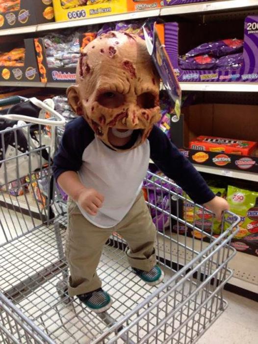 bebé con una máscara de noche de brujas en la cabeza