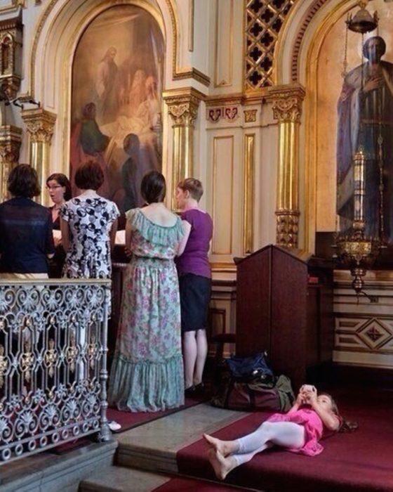 niña acostada en el piso de la iglesia aburrida