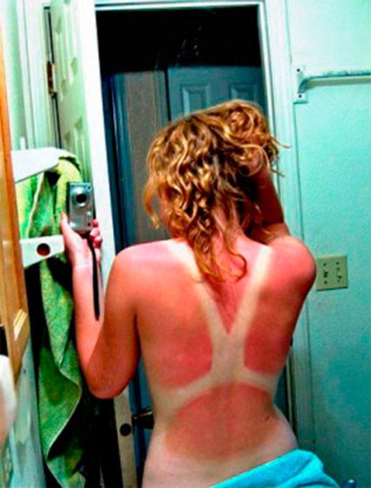 mujer se toma una foto para ver cómo es que le quedo su espalda despues de un buen día de sol