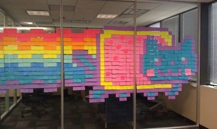 un gato hecho de puros post it de colores en una oficina