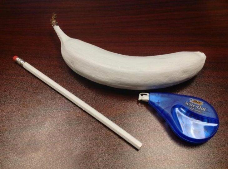 Plátano y lápiz forrado con un corrector de papel