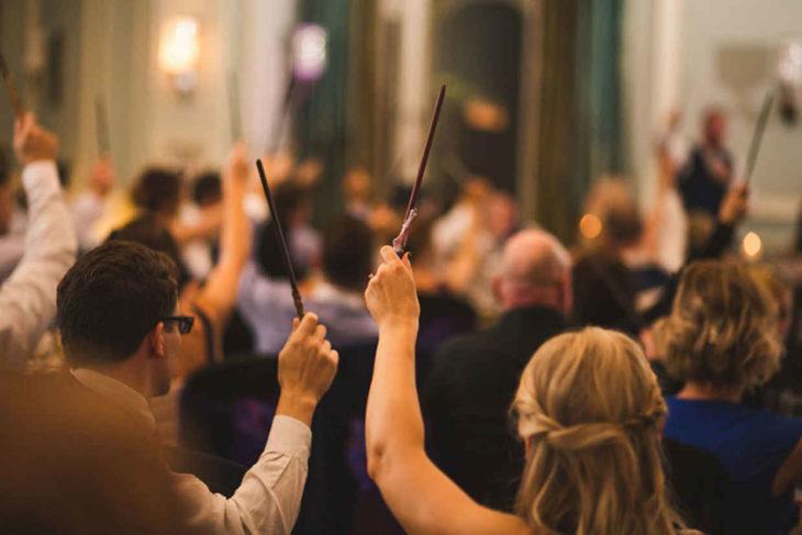 invitados de la boda al estilo Harry Potter con varitas mágicas en sus manos