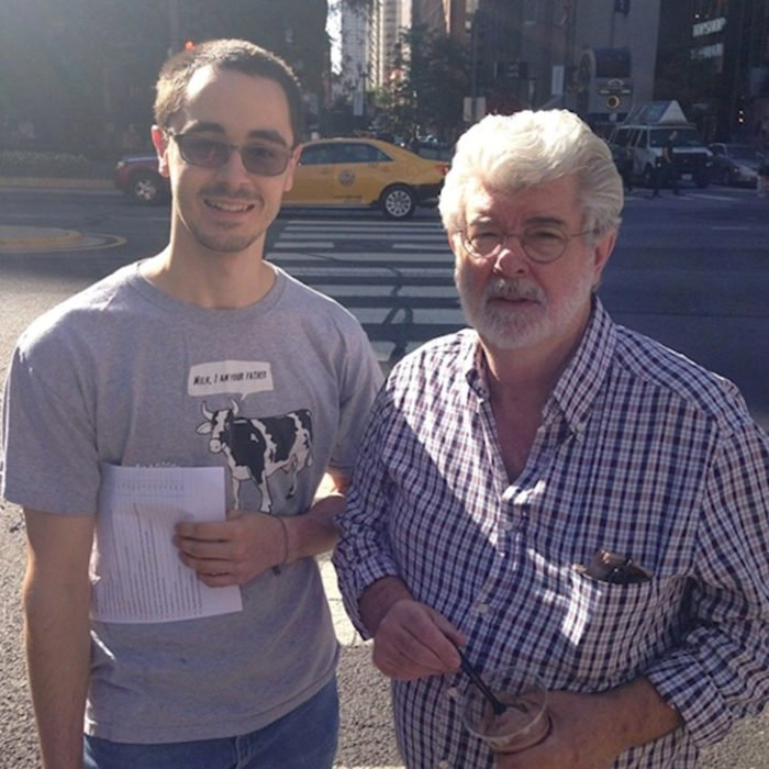 """George Lucas Creador de las salgas fílmicas de Star Wars a lado de un chico con una playera de una vaca que dice """"Leche, yo soy tu padre"""""""