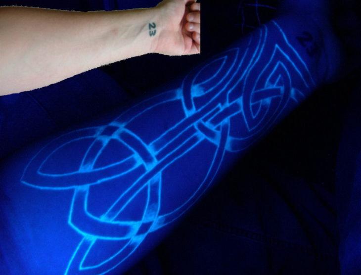 tatuaje fluorescente en un brazo con lineas