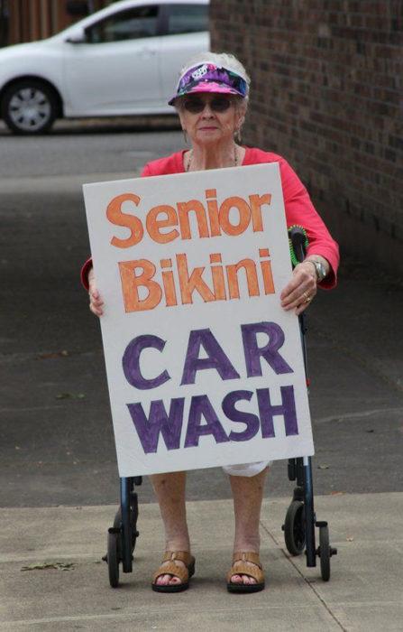 Abuela con letrero que dice lavado de autos para adultos mayores