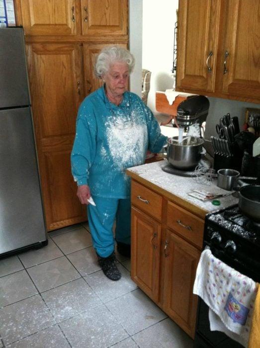 Abuela llena de harina mientras ve su batidora eléctrica