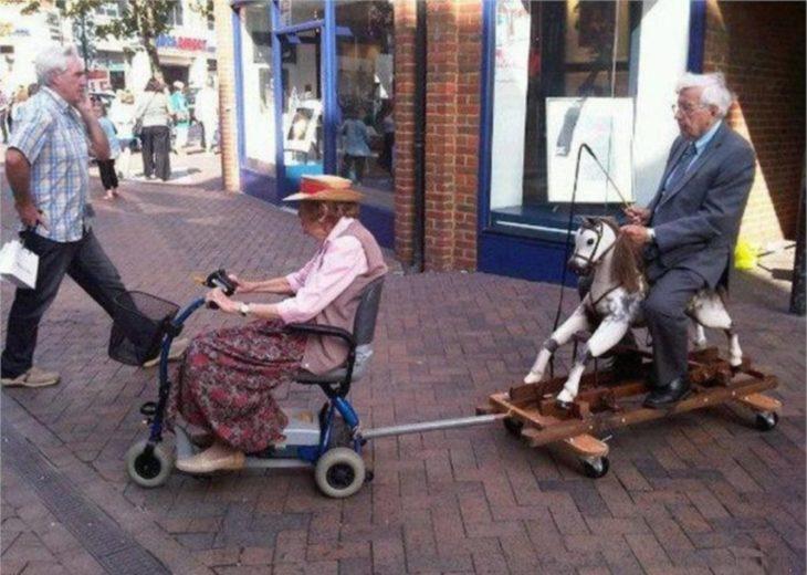 Abuela con su silla de ruedas mecánica y con ella jala un carrito en donde va un caballito de juguete y en él va montado el abuelo