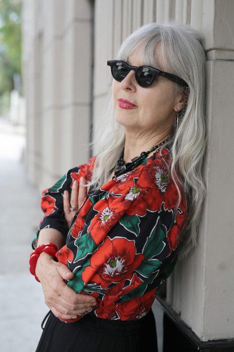 Mujer de +60 años con camisa floreada rojo y negro