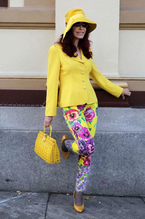 Mujer de +60 años con saco amarillo, sombrero amarillo y pantalón floreado