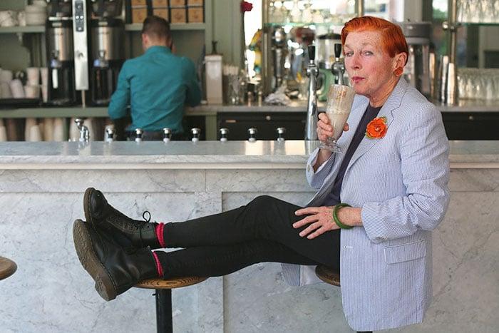 Mujer de +60 años con el cabello rojo, saco y botas y pantalón