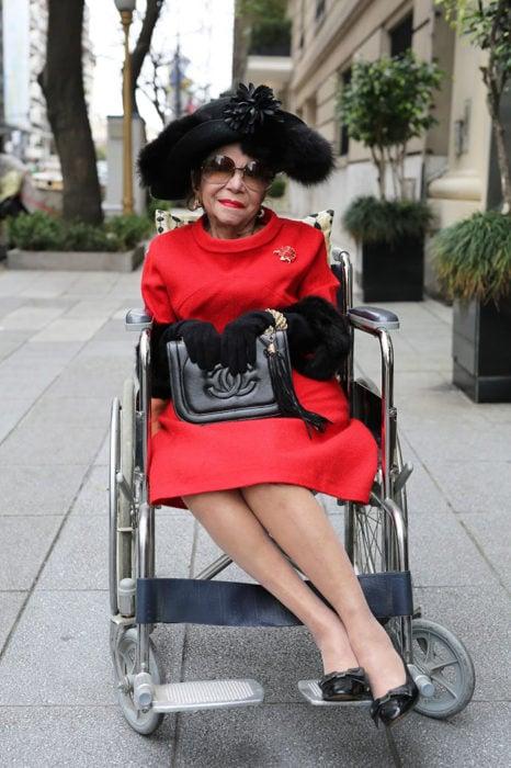 Mujer de +60 años en silla de ruedas vestida muy elegantemente