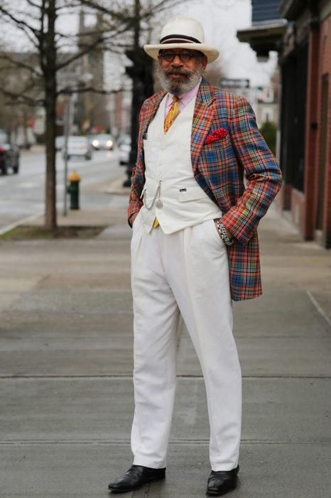 Hombre de +60 años vestido muy elegante con traje blanco y abrigo de colores