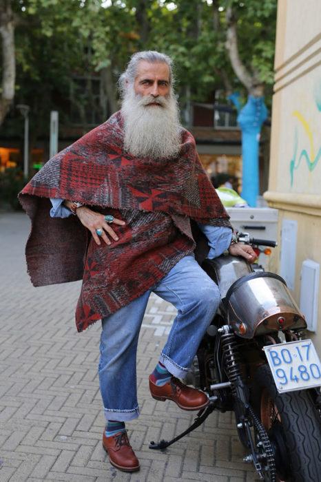 Hombre de +60 años con estilo hippie y barba blanca larga en una moto