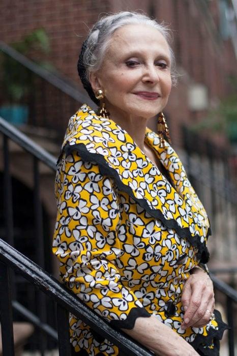 Mujer de +60 años muy guapa vestida con un saco amarillo y negro