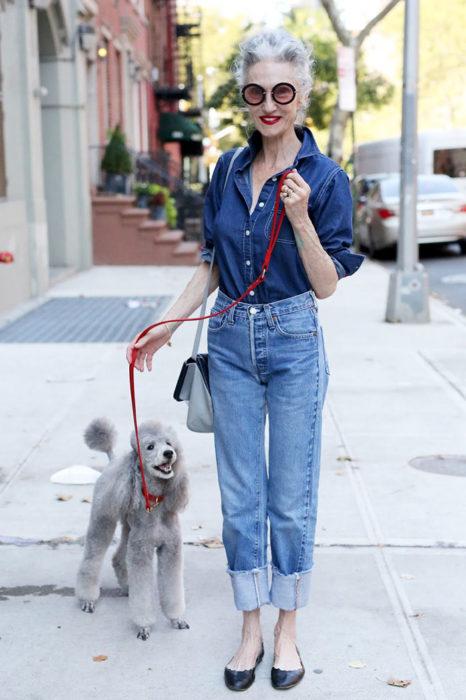 Mujer de +60 años vestida muy trendy con ropa de mezclilla mientras pasea a su perro Poodle