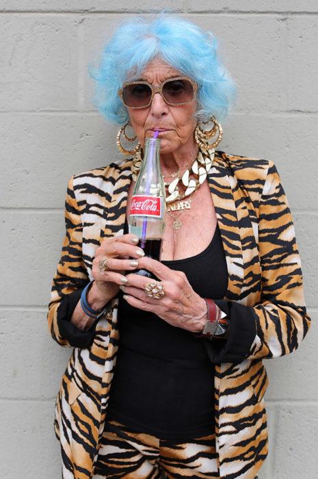 Mujer de +60 años tomando una coca con el cabello azul vestida a la moda