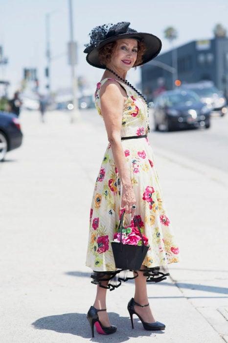 Mujer de +60 años muy guapa con un vestido floreado, sombrero negro, zapatos negros altos