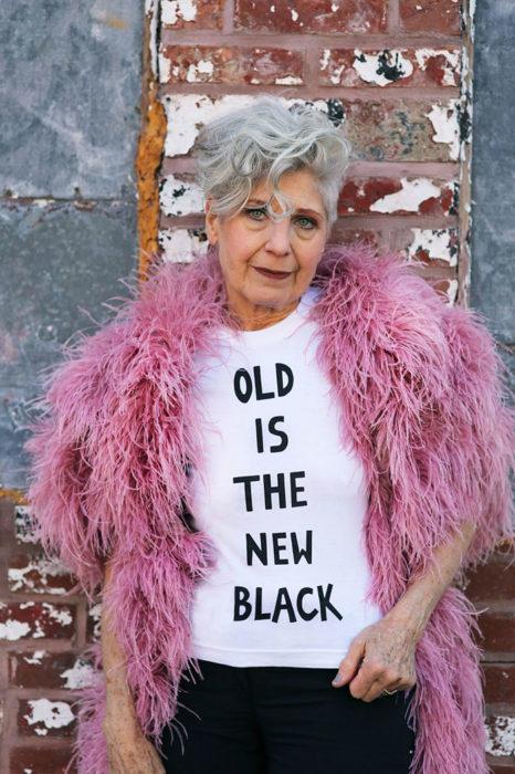 Mujer de +60 años usando una playera que dice VIEJO ES EL NUEVO NEGRO