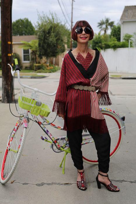 Mujer de +60 años con ropa negra y roja en una bici