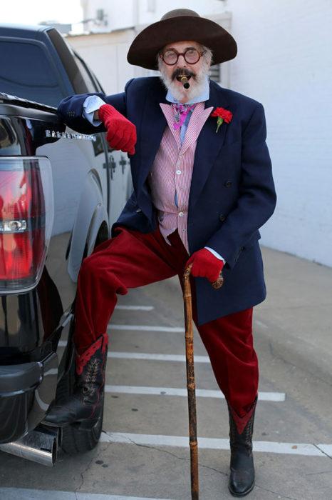 Hombre de +60 años con sombrero, puro, guantes rojos, pantalón rojos, botas, saco azul y camisa rosada