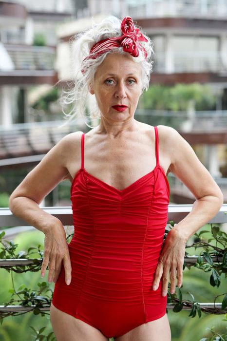 Mujer de +60 años posando con un traje de baño roja