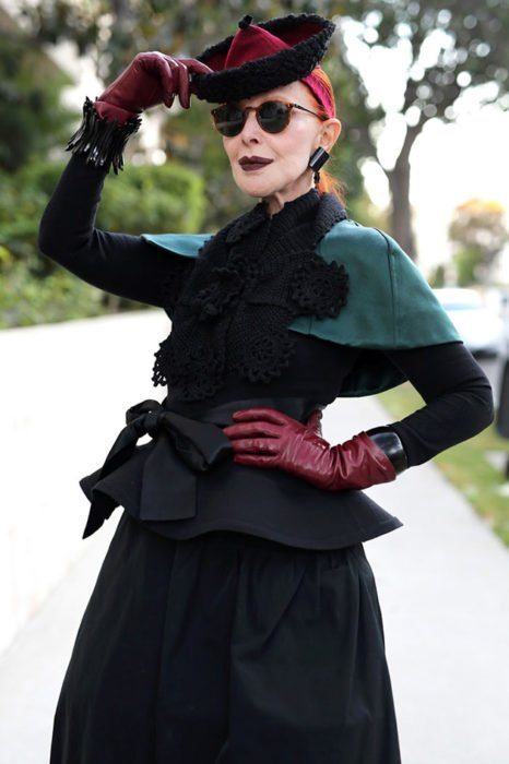 Mujer de +60 años con lentes, sombrero, guantes de piel, falda negra