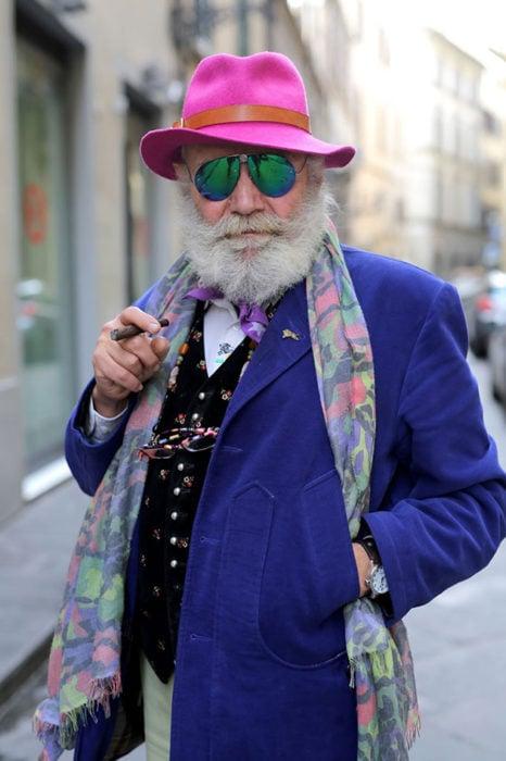 Hombre de +60 años con saco azul rey, sombero rosa, mascada, chaleco negro de colores, lentes y puro
