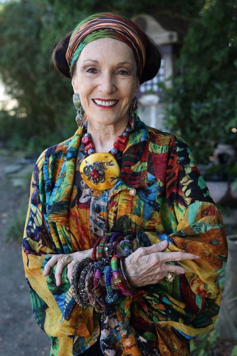 Mujer de +60 años sonriendo mientras luce muy elegante con ropa muy colorida
