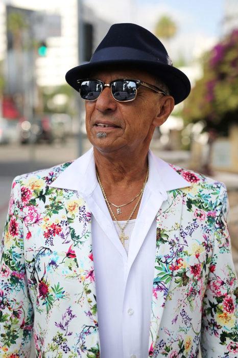 Hombre de +60 años con saco de flores y sombrero negro