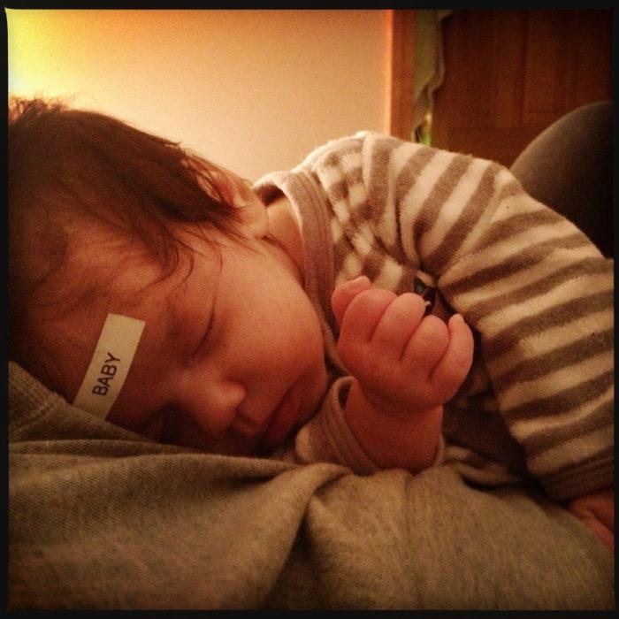 Hombre pone una etiqueta que dice BEBÉ en la frente de su bebé