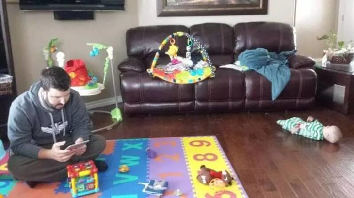 Hombre se entretiene jugando en la alfombra de juegos del bebé mientras el bebé está boca arriba en el piso