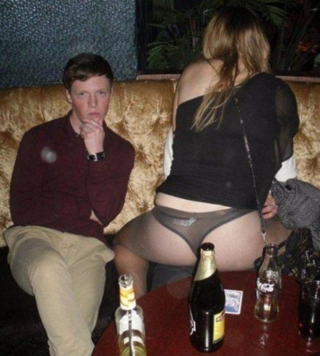 Antro. Imagen de una pareja en el antro en pleno romance mientras un chico está sentado a su lado posando para la foto