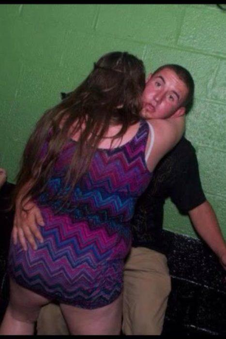 Antro. Foto de chica abrazando a chico mientras este tiene cara de no saber cómo quitársela de encima