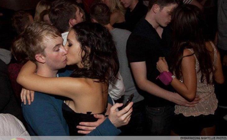 Antro. Foto de un chico que, mientras besa a una chica, está revisando su celular