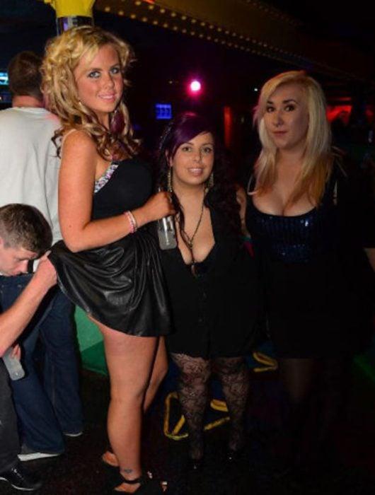 Antro. Foto de tres chicas pero a una de ellas un chico le está levantando el vestido