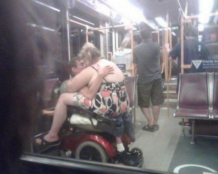 Hombre en silla de ruedas con mujer gorda encima de él mientras se besan