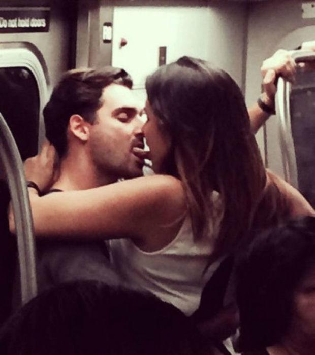 Hombre y mujer besándose con la lengua en el metro