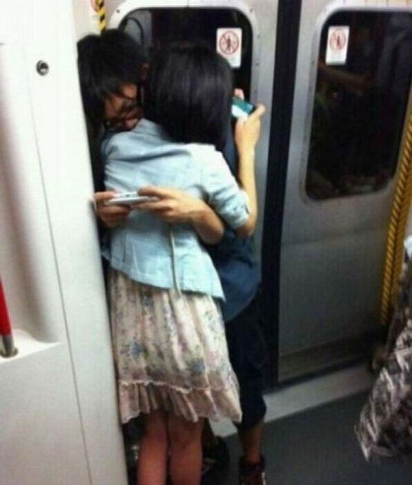 Jóvenes en el metro abrazados mientras están con sus celulares