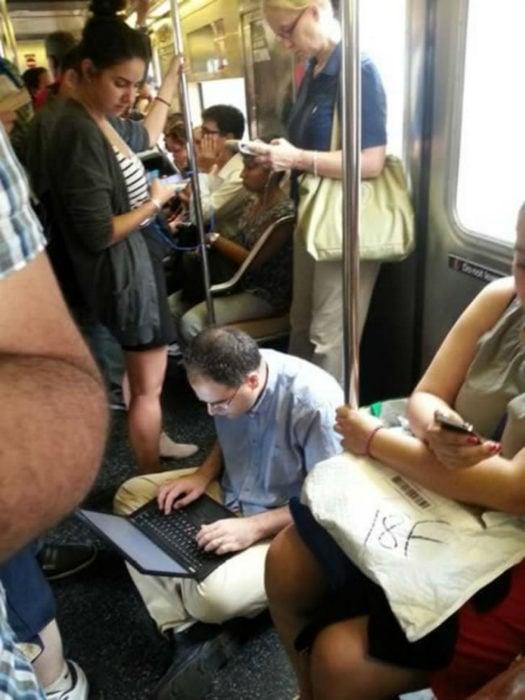 Hombre sentado en el piso del metro con su computadora