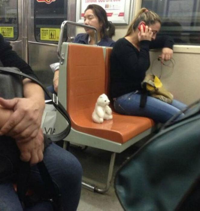 Mujer en el metro hablando por teléfono, el asiento del lado va ocupado por su oso de peluche