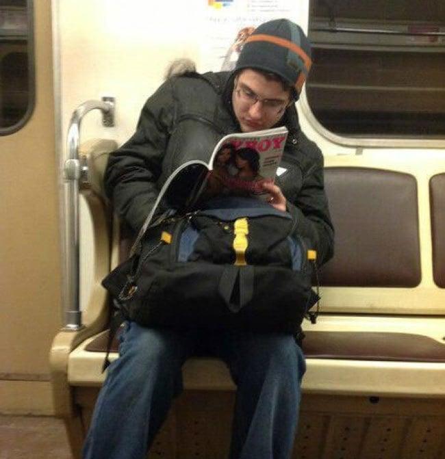 Joven en el metro viendo una Playboy y con su mano dentro de su pantalón