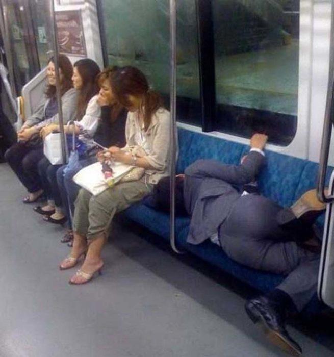 Hombre en traje acostado a sus anchas en el metro